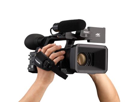 Schwarze, professionelle Videokamera von vorne, von Händen getragen